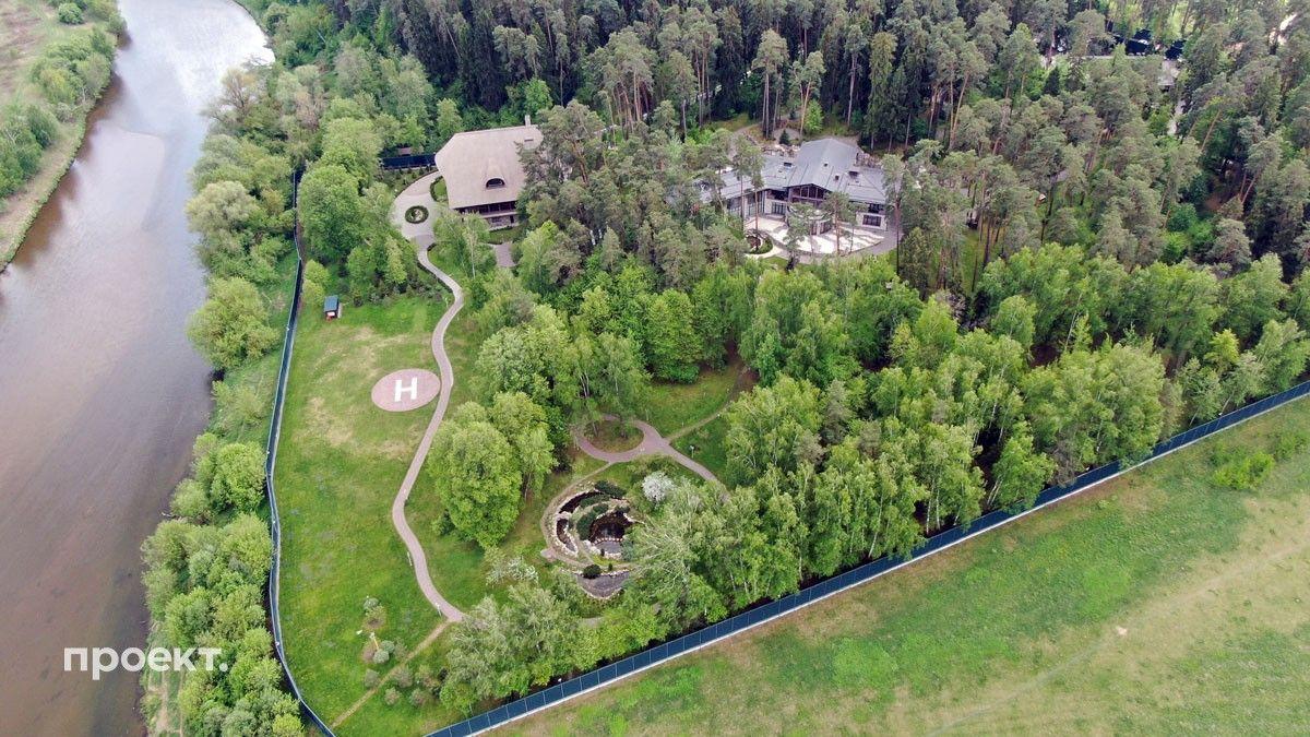 Огромный участок Горки 10-5 — почти шесть гектаров — надежно скрыт за высокими соснами, видны лишь главный дом (всего на участке три дома) и вертолетная площадка
